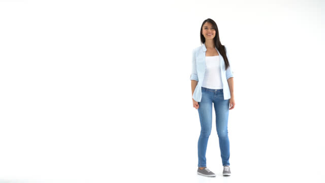 Woman walking into a white background studio and showing something