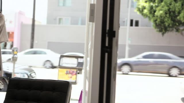 vidéos et rushes de woman walking into clothing store and waving - boutique