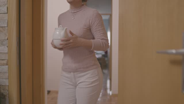 woman walking into her living room carrying a tea pot for afternoon tea - one mature woman only stock videos & royalty-free footage