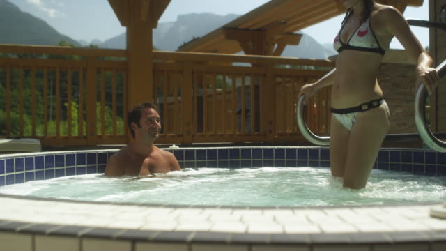MS DS Woman walking into hot tub and sitting with man / Squamish, British Columbia, Canada