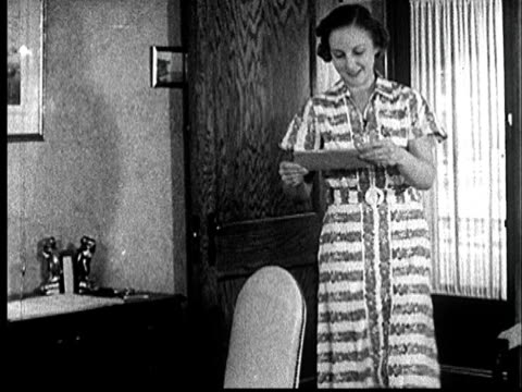 1935 ms pan woman walking into room with a letter/ woman sitting down at desk and opening letter/ / audio - message stock videos & royalty-free footage