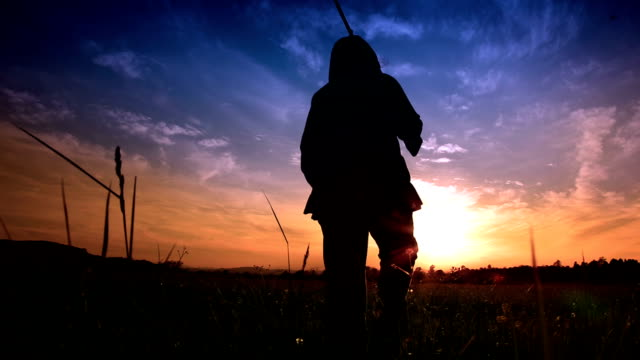 hd - woman walking into sunset with rifle - hunting sport stock videos & royalty-free footage