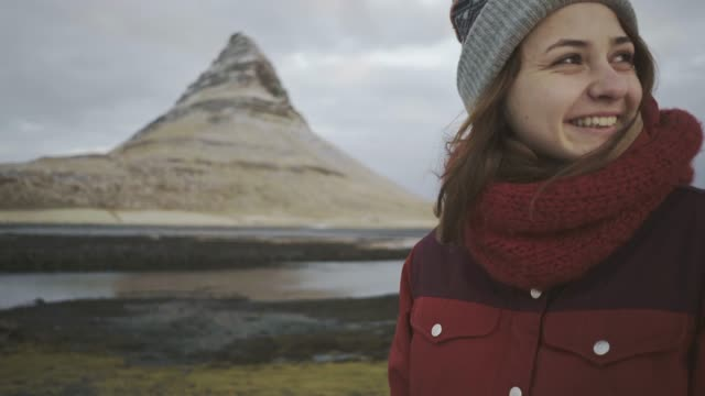 Mujer caminando cerca de Kirkjufell montaña en invierno