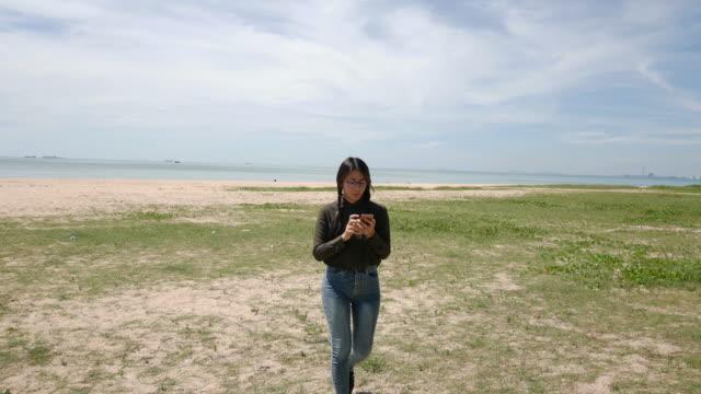 stockvideo's en b-roll-footage met vrouw wandelen in de buurt van het strand met haar mobiele telefoon - ingesproken bericht