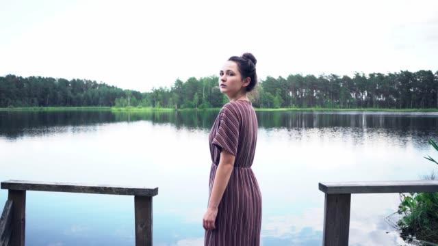 夏に湖の近くを歩く女性 - 低湿地点の映像素材/bロール