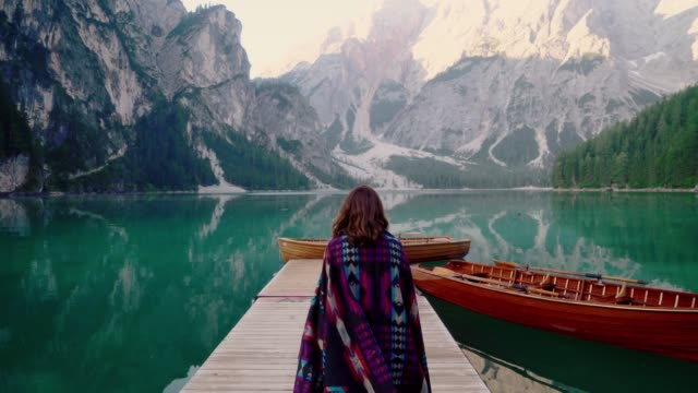 woman walking near the lake lago di braies  in dolomites - travel destinations stock videos & royalty-free footage