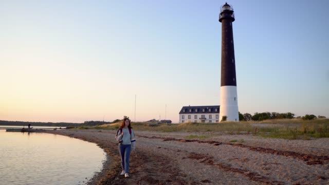 frau zu fuß in der nähe des leuchtturms am strand bei sonnenuntergang - ostsee stock-videos und b-roll-filmmaterial