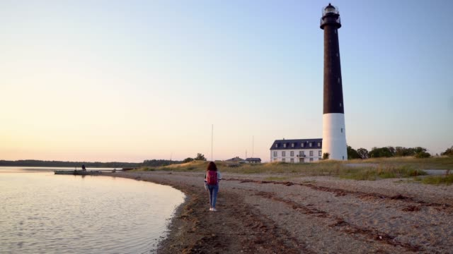 woman walking near the lighthouse on the beach at sunset - lighthouse stock videos & royalty-free footage