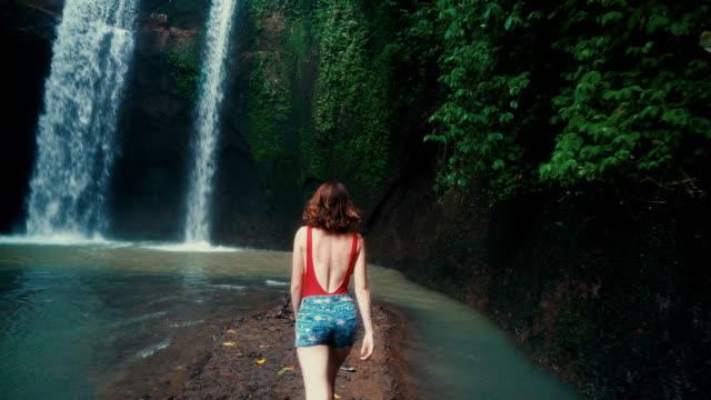 stockvideo's en b-roll-footage met vrouw lopen in de buurt van tibumana waterval in bali, indonesië - bali