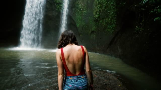 vídeos y material grabado en eventos de stock de mujer caminando junto a la cascada de tibumana en bali, indonesia - bali