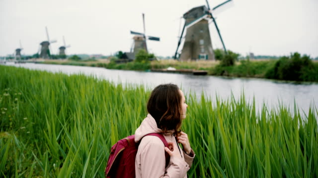 woman walking near windmills in the netherlands - holland stock videos and b-roll footage
