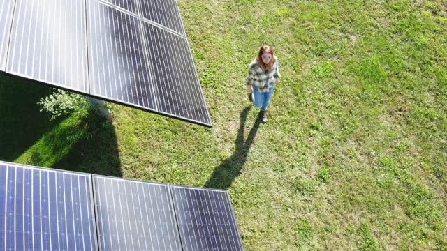 vídeos y material grabado en eventos de stock de woman walking next to solar panels on farm - recursos sostenibles