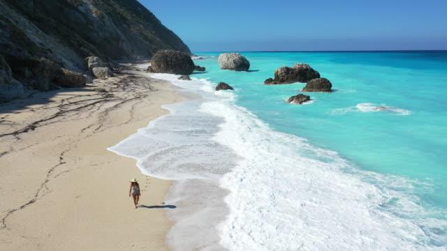 woman walking om megali petra beach, lefkada, greece. - straw hat stock videos & royalty-free footage