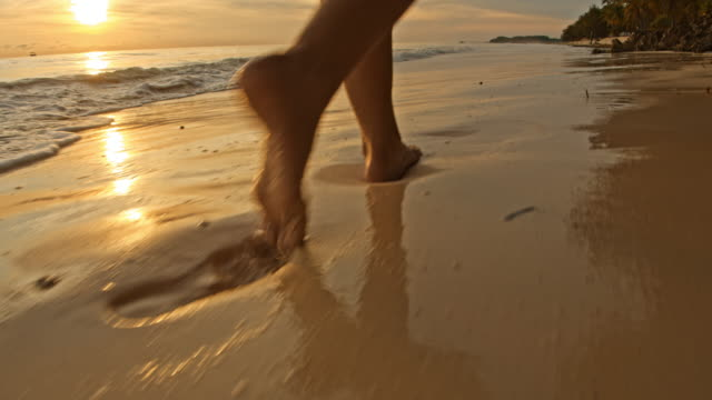 slo mo woman walking on a beach at sunset - barefoot stock videos & royalty-free footage