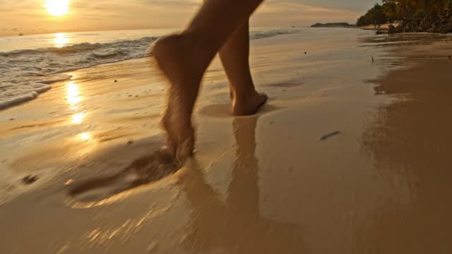 slo mo frau zu fuß an einem strand bei sonnenuntergang - barfuß stock-videos und b-roll-filmmaterial