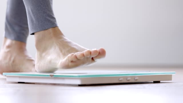 woman walking on a body weighing scale - weight scale stock videos & royalty-free footage