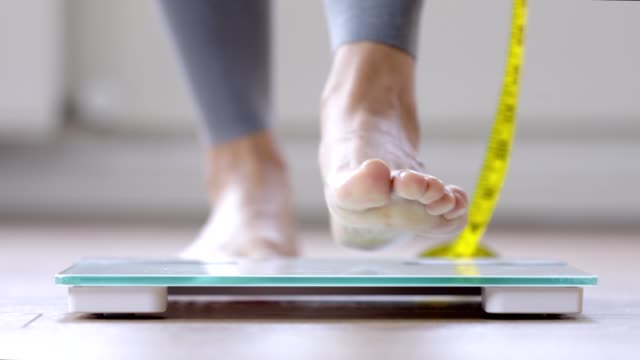 woman walking on a body weighing scale - tape measure stock videos & royalty-free footage