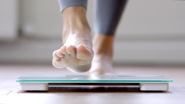 woman walking on a body weighing scale - trousers stock videos & royalty-free footage