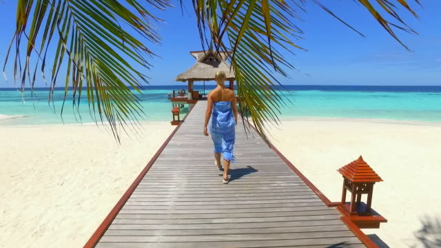 A woman walking on a dock pier over a tropical island beach. - Slow Motion