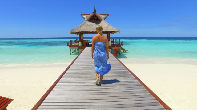 a woman walking on a dock pier over a tropical island beach. - slow motion - blonde hair stock videos & royalty-free footage