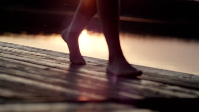 woman walking on a lake pier. lake sunset - plank stock videos & royalty-free footage