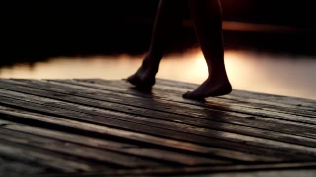kvinnan promenader på en sjö brygga. lake sunset - angöringsbrygga bildbanksvideor och videomaterial från bakom kulisserna