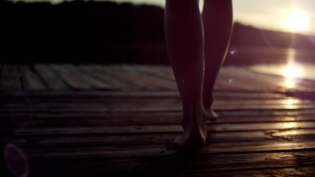 woman walking on a lake pier. lake sunset - jetty stock videos & royalty-free footage