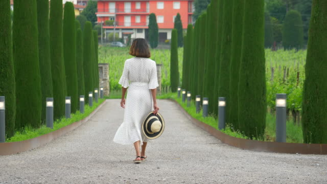 vídeos de stock, filmes e b-roll de a woman walking on a path with cypress trees while traveling at a luxury resort in italy, europe. - slow motion - hat