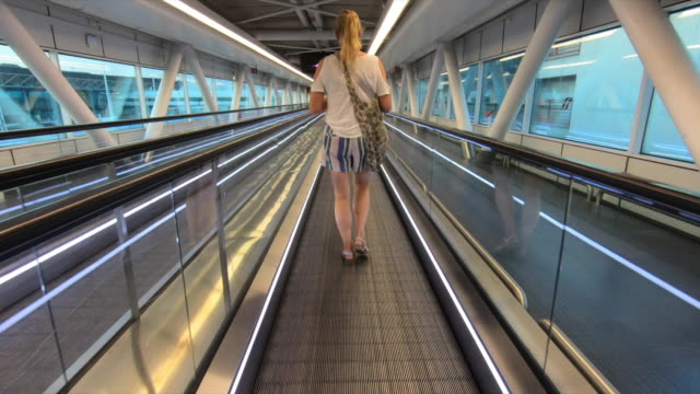 a woman walking on a people mover moving walkway at the airport in rome, italy, europe. - slow motion - stazione ferroviaria video stock e b–roll
