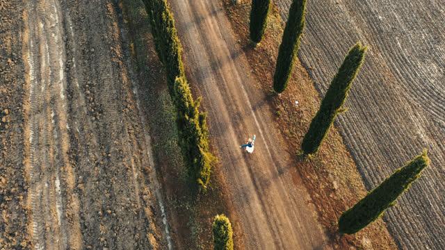 vídeos y material grabado en eventos de stock de aerial mujer caminando por una carretera llena de cipreses que conduce a una villa de vacaciones en toscana - multicóptero