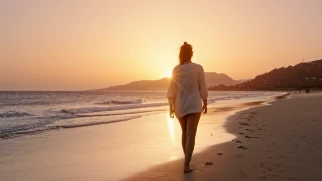 Femme qui marche sur une plage au coucher du soleil