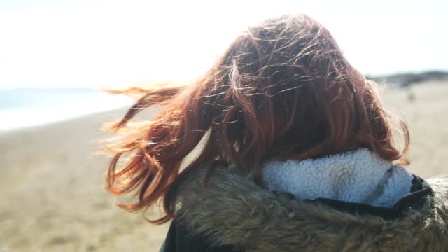 Woman Walking on Beach, Red Hair Blowing in Breeze