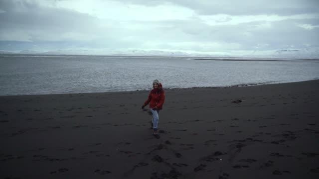 vidéos et rushes de femme qui marche sur la plage de sable noir en islande - manteau et blouson d'hiver