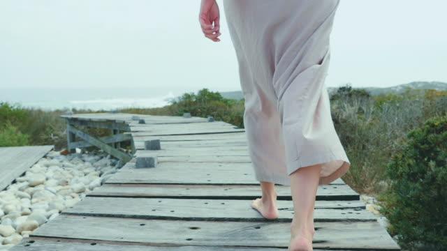 vídeos de stock, filmes e b-roll de woman walking on boardwalk - cabelo preso