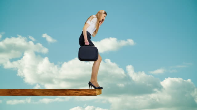 Woman walking on edge of plank