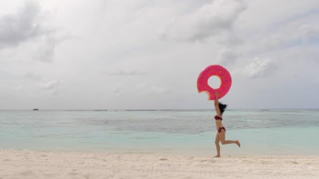 ビキニを着て熱帯のビーチの休日に夏休みを楽しむ巨大な膨脹可能なリングを保持して空のビーチを歩く女性 - 浮き輪点の映像素材/bロール
