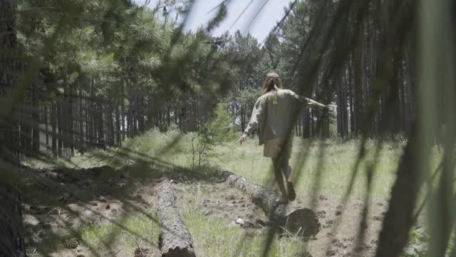 vídeos y material grabado en eventos de stock de woman walking on fallen log - menos de diez segundos