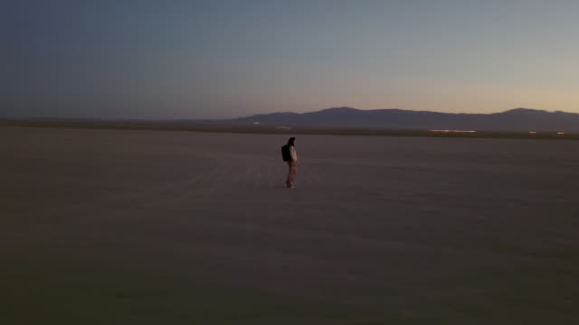 Woman walking on flat landscape of Mojave Desert