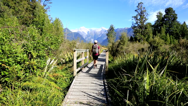 Woman walking on footpath around Lake Matheson, Westland National Park