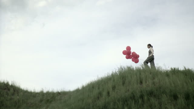Woman walking on hill with bunch of balloons, then stopping and letting them float away