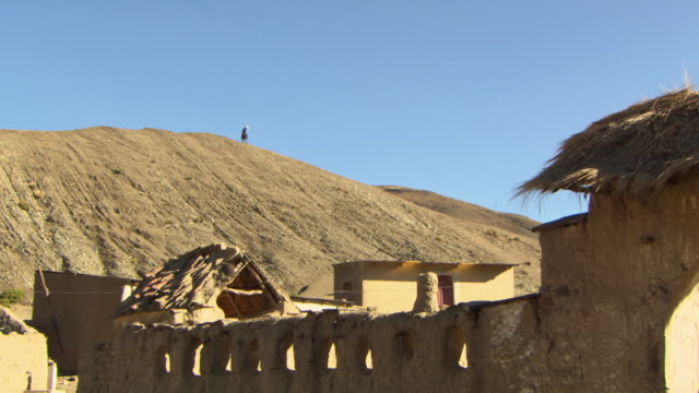woman walking on hilltop in traditional outfit, with traditional straw huts and wall in f/g, small rural town, potolo, bolivia - ボリビア点の映像素材/bロール