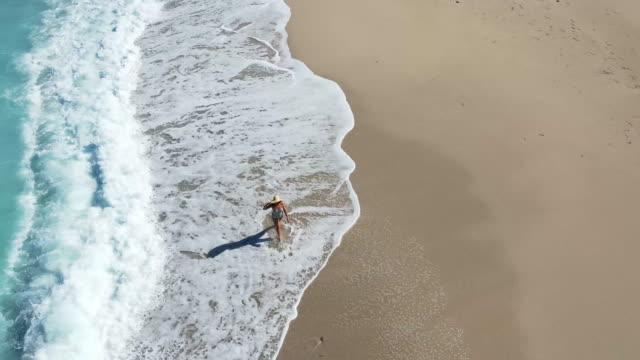 woman walking on megali petra beach, lefkada, greece. - straw hat stock videos & royalty-free footage