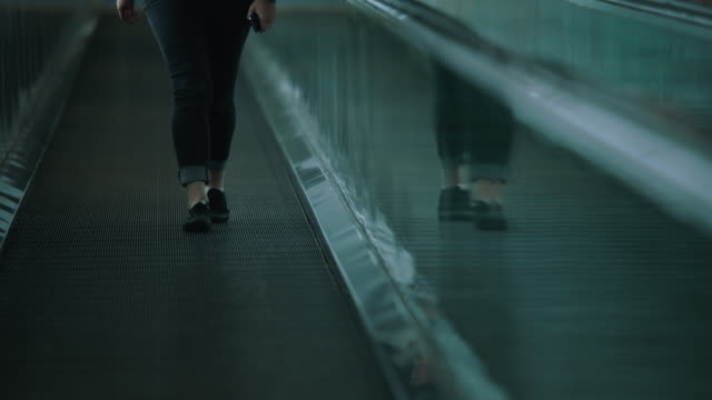 ms pan woman walking on moving walkway at sfo - human leg stock videos and b-roll footage