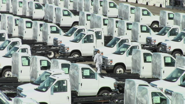 ws, ha, woman walking on parking lot full of white delivery trucks, ohio, usa - fleet of vehicles stock videos and b-roll footage