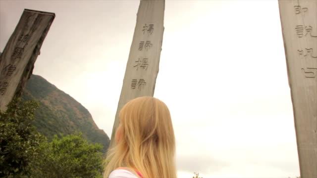 woman walking on path of wisdom, lantau island hong kong - lantau stock videos and b-roll footage