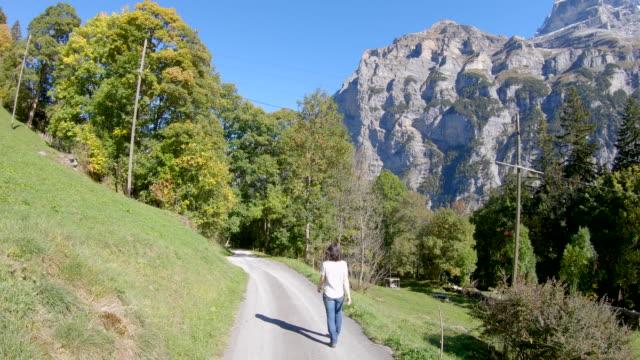 高山の風景の中の舗装道路の上を歩く女性 - 中年の女性一人点の映像素材/bロール