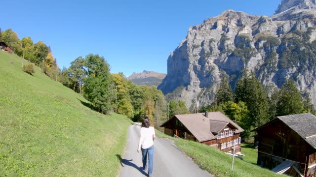 stockvideo's en b-roll-footage met vrouw lopen op de verharde weg in alpine landschap - alleen oudere vrouwen