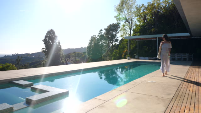 ws woman walking on pool deck in backyard of modern home - home ownership stock videos & royalty-free footage