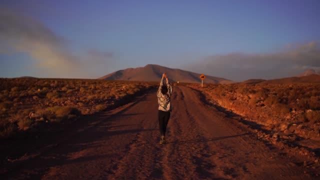 vídeos y material grabado en eventos de stock de mujer caminando por carretera en el desierto de atacama en chile - tourism