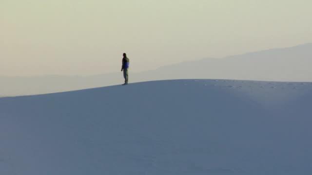 WS ZO PAN Woman walking on sand dunes / Alamogordo, New Mexico, USA